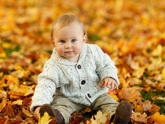 Niño sentado en hojas marrones explorando el entorno