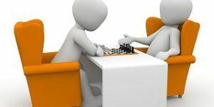Dos personas de dibujos jugando al ajedrez
